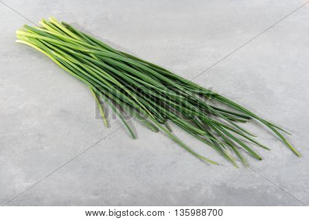 Fresh green chives on grey background