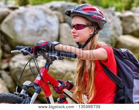 Bikes bicyclist girl. Girl wearing bicycle helmet and glass with rucksack ciclyng road bicycle. Looks down.