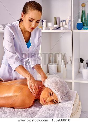 Woman middle-aged take back massage in spa salon with young beautician.