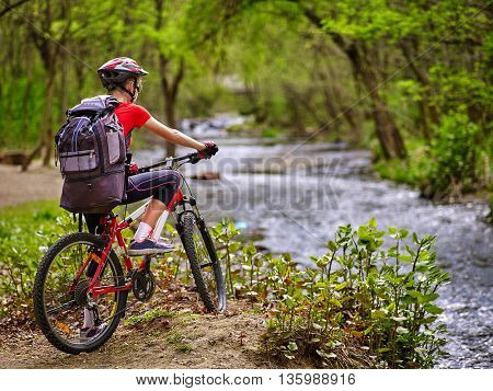 Bikes cycling girl. Girl with big rucksack rides bicycle. Girl cycling fording throught water . Cycling trip is good for health. Cyclist is looking throught river.