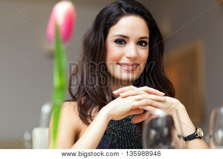 Smiling beautiful woman having dinner in a restaurant. Flower in the foreground