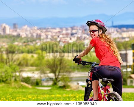 Bikes cycling girl. Girl rides bicycle into city. Girl in cycling. Cycling is good for health. Cyclist is looking at city in distance.