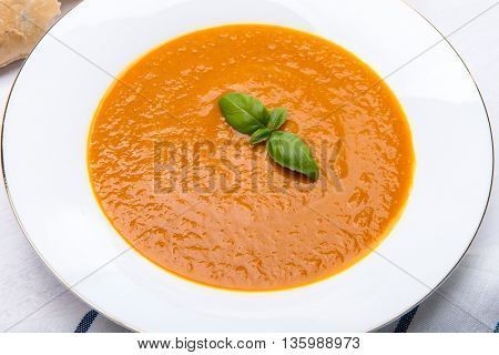 White bowl of squash soup with basil leaf