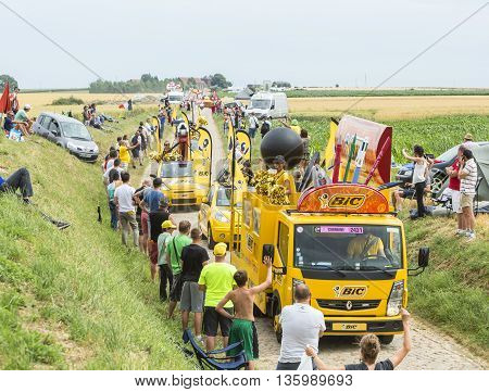 QuievyFrance - July 07 2015: BIC caravan during the passing of the Publicity Caravan on a cobblestone road in the stage 4 of Le Tour de France on July 7 2015 in Quievy France. BIC is a global company which offers an extensive line of writing and office to