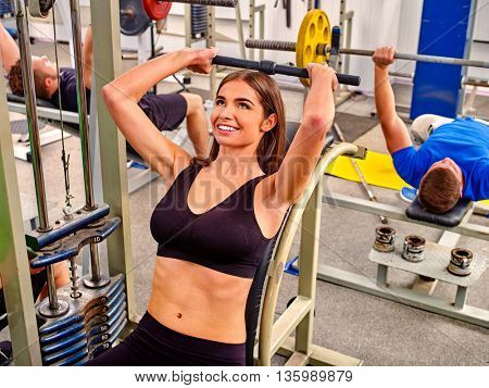 Woman working his arms and chest at gym. Bicep curl machine.