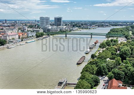 Bridges over the Danube river in Bratislava city Slovak republic. Docks scene. Old bridge and Apollo bridge. Ship transportation. High-rise buildings. Travel destination.