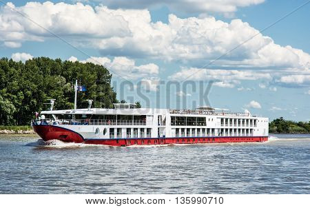 Cruise ship and Danube river. Travelling scene. Beautiful place. Travel destination. Clouds in the sky. Seasonal outdoors scene. Summer vacation. Tourism theme.