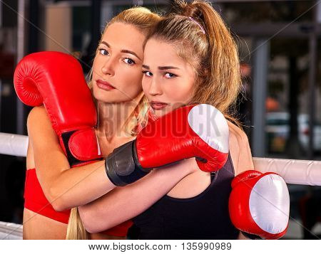 Two women boxer wearing red gloves posing in ring.