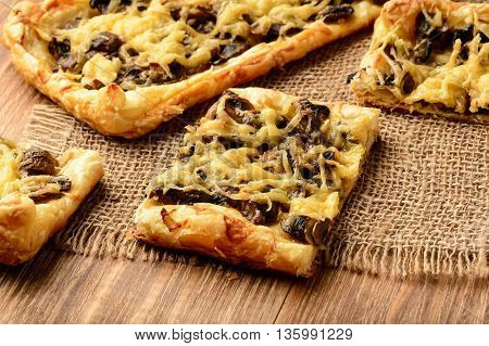 Puff pastries with mushrooms and cheese on wooden background.