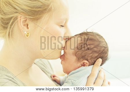 A mother kissing her newborn child on his forehead