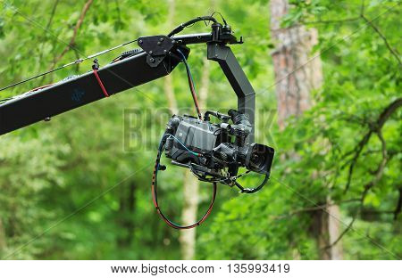 Professional camera on a telescopic arm with a green blurred background.