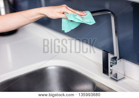 Cropped hand of woman wiping faucet by sink in kitchen