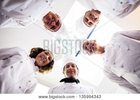 Portrait of chefs team standing in a circle wearing uniforms in a kitchen