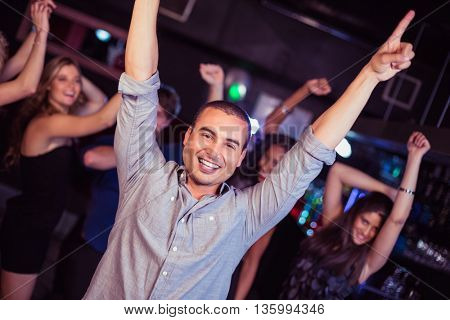 Cute friends having fun and dancing in a nightclub