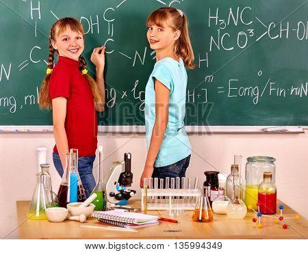 Happy children holding flask in chemistry class. Children written on chemistry blackboard.