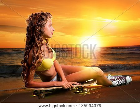 Beautiful and fashion young woman posing at sunset with skateboard. Rest after riding on skateboard