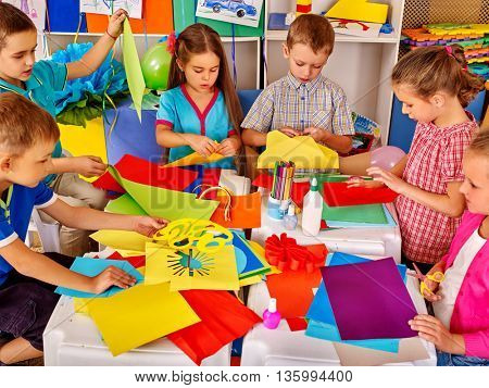 Group kids holding colored paper on table in kindergarten . Children writting letter Santa Claus.