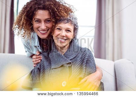 Portrait of happy woman cuddling mother in living room