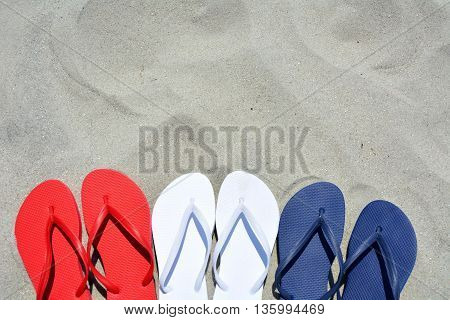 Red white and blue flip flops on the sand. Plenty of room for your text