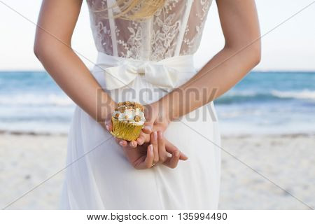 Bride with a beautiful lace dress holding a cupcake