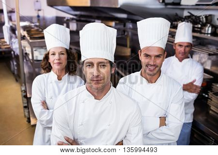 Group of happy chefs smiling at the camera in a kitchen wearing uniforms