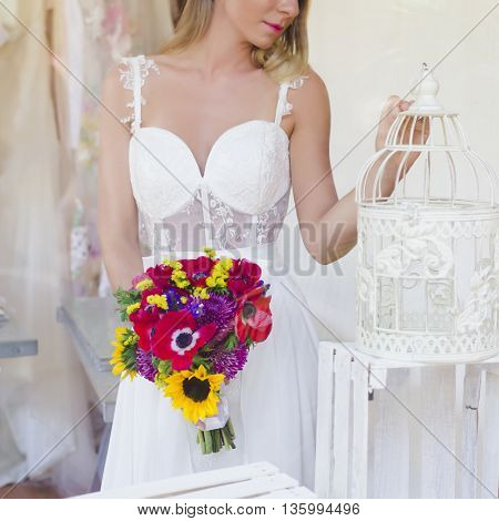 Beautiful bride with bouquet indoors