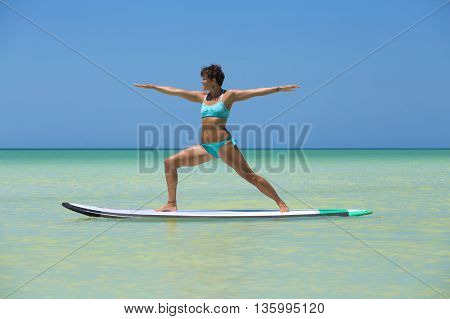 Woman practicing yoga on a stand up paddle board in the Mexican Caribbean