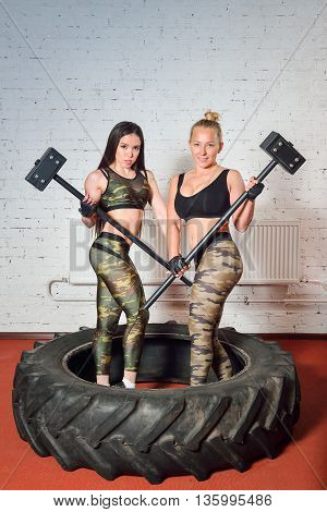 Fit women with huge hammers posing in gym .