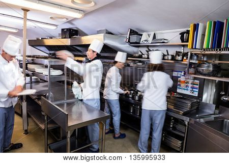 Team of chefs preparing food in the kitchen of a restaurant