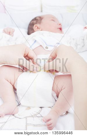Woman changing the diaper of a newborn
