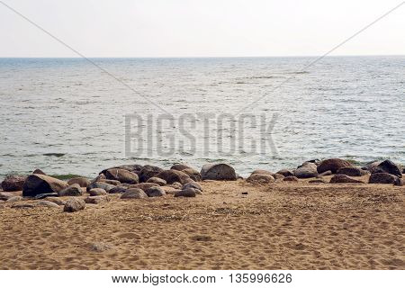 the beach of the Gulf of Finland in Saint-Petersburg with sand and stones in grey, cool weather in the fall