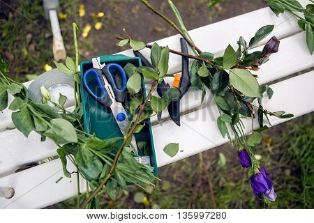 accessories scissors, shears lie on the bench with a cut-off branches flowers