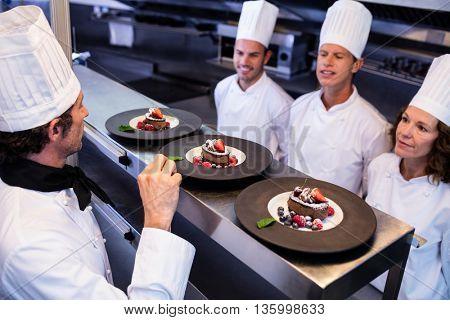 Head chef inspecting dessert plates at order station in restaurant