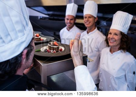 Head chef showing his thumbs up after inspecting dessert plates in restaurant