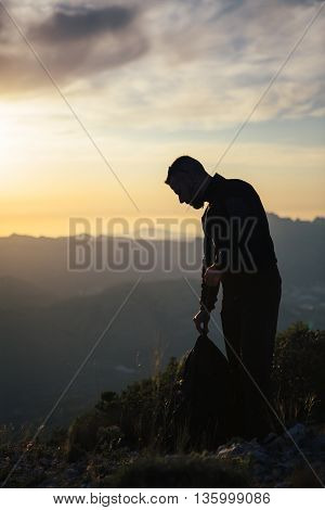 Side view of adult backpacker looking down against of evening mountains.Copy space. Backlighting