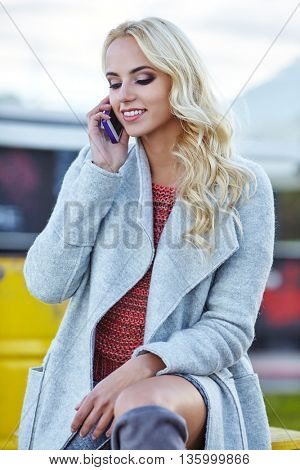 Happy woman  using a smart phone on the street in autumn day