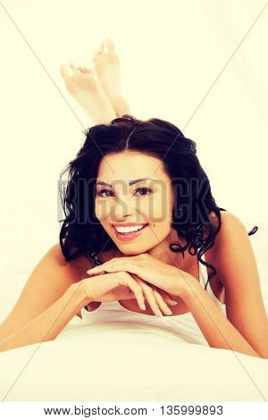 Happy young woman lying in bed and smiling to camera