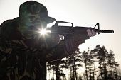 picture of ar-15  - a soldier standing up pointing a rifle foward covered with camouflage with the sun shining through - JPG