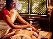 Постер, плакат: Woman having ayurvedic massage with pouch of rice Passage to massage India