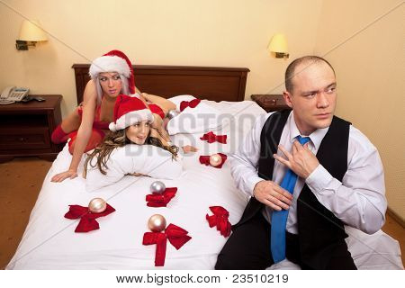 Young Santa ladies waiting their boss in bed decorated by decorated Christmas balls