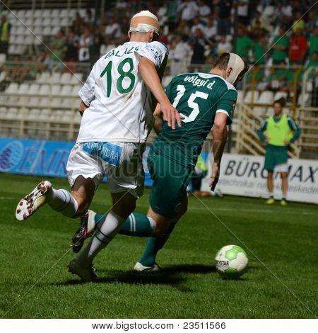 KAPOSVAR, HUNGARY - SEPTEMBER 10: Benjamin Balazs (in white) in action at a Hungarian National Championship soccer game - Kaposvar (white) vs Gyor (green) on September 10, 2011 in Kaposvar, Hungary.