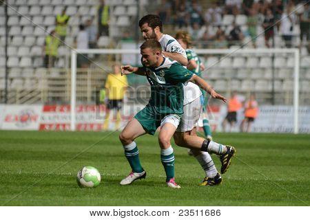 KAPOSVAR, HUNGARY - SEPTEMBER 10: Pedro Sass (white 33) in action at a Hungarian National Championship soccer game - Kaposvar (white) vs Gyor (green) on September 10, 2011 in Kaposvar, Hungary.