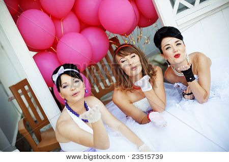 Group of happy brides of 60s style sending air kiss