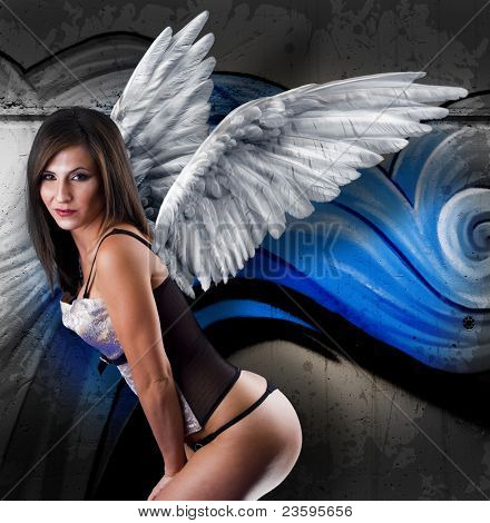 Beautiful young woman with white wings against graffiti wall.