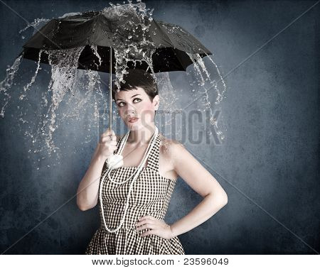 Pin-up girl with umbrella under water splash