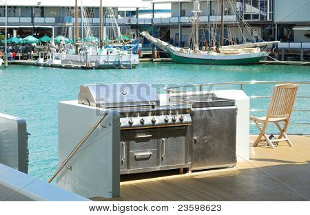 luxury gas  barbecue on the ship deck with background of sails