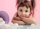 Portrait Of A Cute Little Girl With Marshmallow On Pink Background. poster