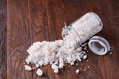 Spa Concept. Bath Salt Pouring Out Of Glass Jar On Wooden Table, Close-up, Selective Focus. Skin And poster