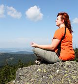 pic of witch-doctor  - Young woman meditating on a high peak - JPG
