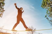A Man, Aged With A Beard And Wearing Sunglasses, Balances On A Slackline In The Open Air Between Two poster